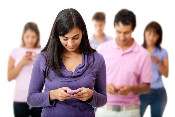 Group of young people texting on their mobile phones